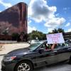 教師舉著「多少學生得送死?」標語,抗議貿然重啟學校