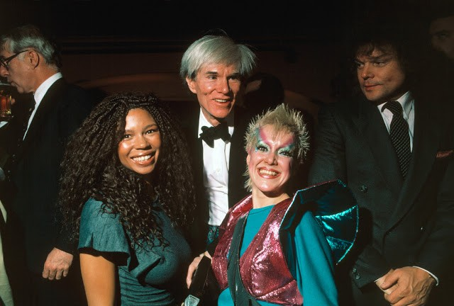 """Andy WARHOL with groupies in Manhattan's Xenon night club. """"High Voltage"""" is at right."""