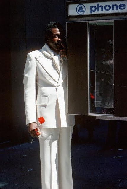 Man at a telephone booth on Fifth Avenue.