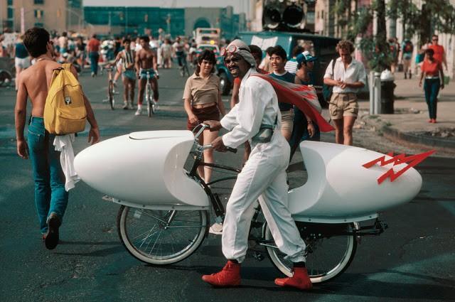 USA. New York City. 1983. A man walks on Fifth Aveneue with a homemade speed bike.
