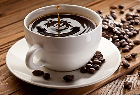Drop falling into a cup of coffee. On a wooden background; Shutterstock ID 75941575; PO: aol; Job: production; Client: drone