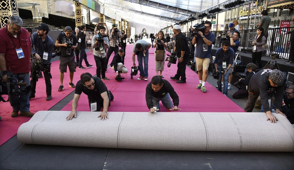 Workmen are trailed by photographers as they roll out the red carpet for the Oscars in front of the Dolby Theatre on Wednesday, Feb. 24, 2016, in Los Angeles. The 88th Academy Awards will be held on Sunday (Photo by Chris Pizzello/Invision/AP)