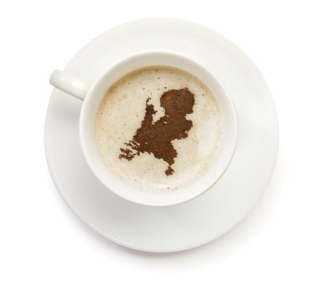 A top shot of a cup of coffee with froth and powder in the shape of Netherlands (Europe).(series) How about having a break :)